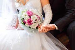 Η νύφη και ο νεόνυμφος κρατούν υπό εξέταση μια γαμήλια ανθοδέσμη Στοκ φωτογραφία με δικαίωμα ελεύθερης χρήσης