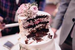 Η νύφη και ο νεόνυμφος κόβουν στενό τον επάνω γαμήλιων κέικ στοκ εικόνα