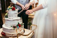 Η νύφη και ο νεόνυμφος κόβουν το αγροτικό γαμήλιο κέικ στο γαμήλιο συμπόσιο με Στοκ Εικόνες