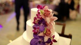 Η νύφη και ο νεόνυμφος κόβουν το κέικ με τα φρέσκα λουλούδια φιλμ μικρού μήκους