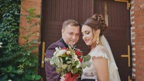 Η νύφη και ο νεόνυμφος με μια φωτεινή ανθοδέσμη στα χέρια μαζί κοντά σε έναν τουβλότοιχο με την ανάπτυξη των κλάδων των σταφυλιών απόθεμα βίντεο