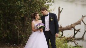 Η νύφη και ο νεόνυμφος μιλούν κοντά στον ποταμό και το παλαιό δέντρο φιλμ μικρού μήκους