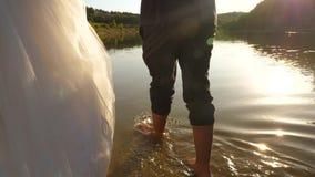 Η νύφη και ο νεόνυμφος πηγαίνουν χωρίς παπούτσια στο νερό στην όχθη ποταμού E ερωτευμένος περίπατος ζευγών στην παραλία χέρι-χέρι απόθεμα βίντεο