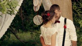 Η νύφη και ο νεόνυμφος που αγκαλιάζουν tenderly στο πάρκο φιλμ μικρού μήκους