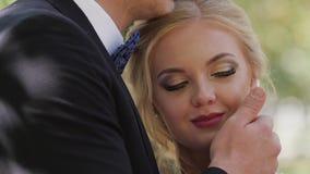 Η νύφη και ο νεόνυμφος που περπατούν στην πόλη μεταξύ των στηλών φιλί και αγκάλιασμα του ζεύγους αγάπης Κινηματογράφηση σε πρώτο  απόθεμα βίντεο