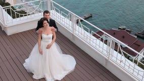 Η νύφη και ο νεόνυμφος που στέκονται σε ένα μπαλκόνι που αγνοεί τη θάλασσα απόθεμα βίντεο