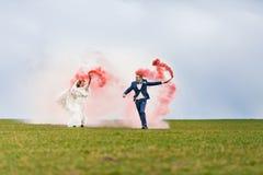 Η νύφη και ο νεόνυμφος που τρέχουν μέσω του τομέα με τις κόκκινες βόμβες καπνού Στοκ φωτογραφία με δικαίωμα ελεύθερης χρήσης