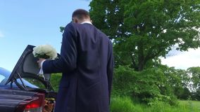 Η νύφη και ο νεόνυμφος στέκονται κοντά στο άσπρο αυτοκίνητο στο ξύλο πεύκων με τον ήλιο φιλμ μικρού μήκους