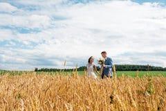 Η νύφη και ο νεόνυμφος στέκονται στον τομέα Στοκ φωτογραφία με δικαίωμα ελεύθερης χρήσης