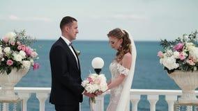 Η νύφη και ο νεόνυμφος στη γαμήλια τελετή Μια νεολαία συνδέει τις ερωτευμένες στάσεις στην αψίδα Γάμος θαλασσίως απόθεμα βίντεο