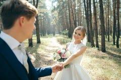 Η νύφη και ο νεόνυμφος στο γάμο ντύνουν στο φυσικό υπόβαθρο ευτυχής εκλεκτής ποιότητας γάμος ημέρας ζευγών ιματισμού Το Newlyweds στοκ φωτογραφίες