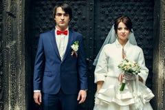 Η νύφη και ο νεόνυμφος φαίνονται σοβαρά στεμένος στην παλαιά πέτρα entranc Στοκ εικόνες με δικαίωμα ελεύθερης χρήσης