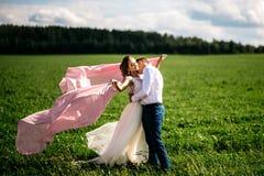 Η νύφη και ο νεόνυμφος φιλούν στον τομέα Στοκ Φωτογραφία