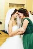 Η νύφη και ο φίλος της φωνάζουν βάζοντας σε ένα πέπλο Στοκ Εικόνες
