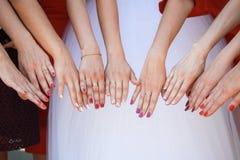 Η νύφη και η στάση φίλων της δίπλα-δίπλα και παρουσιάζουν χέρια τους Στοκ Εικόνες