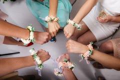 Η νύφη και τα κορίτσια νυφών ` s κάθονται σε έναν κύκλο και κρατούν τις πυγμές τους Χέρια με τα βραχιόλια λουλουδιών Στοκ εικόνες με δικαίωμα ελεύθερης χρήσης