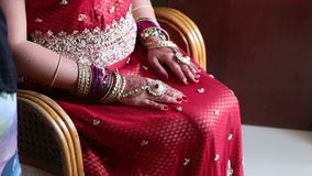 Η νύφη κινηματογραφήσεων σε πρώτο πλάνο στην έδρα κρατά τα χέρια με Henna τα σχέδια στα γόνατα απόθεμα βίντεο