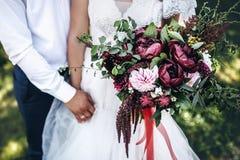 Η νύφη κρατά μια γαμήλια ανθοδέσμη με τα peonies στοκ εικόνες