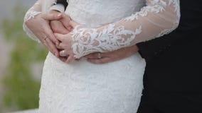Η νύφη κρατά μια γαμήλια ανθοδέσμη στα χέρια, τα αγκαλιάσματα νεόνυμφων αυτή από πίσω Νεόνυμφος που αγκαλιάζει τη νύφη από πίσω Στοκ φωτογραφίες με δικαίωμα ελεύθερης χρήσης