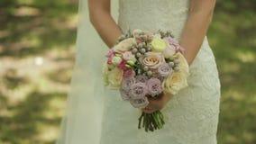 Η νύφη κρατά μια γαμήλια ανθοδέσμη των τριαντάφυλλων νυφικός γάμος ημέρας ανθο& διαφορετικά λουλούδι&alph φιλμ μικρού μήκους