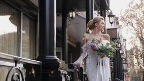 Η νύφη κρατά μια γαμήλια ζωηρόχρωμη ανθοδέσμη στην οδό απόθεμα βίντεο
