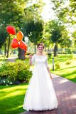Η νύφη κρατά τα κόκκινα μπαλόνια στο χέρι της στοκ φωτογραφίες