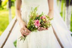 Η νύφη κρατά τη νυφική ανθοδέσμη των ρόδινων flovers στοκ φωτογραφία