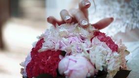 Η νύφη κτυπά τη γαμήλια ανθοδέσμη, σαν εξερευνώντας την, εξέταση, fingering, κινηματογράφηση σε πρώτο πλάνο, σε αργή κίνηση απόθεμα βίντεο