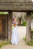 Η νύφη με μια ανθοδέσμη των λουλουδιών που θέτουν στη φωτογραφία στη φύση Στοκ εικόνες με δικαίωμα ελεύθερης χρήσης