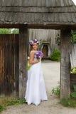 Η νύφη με μια ανθοδέσμη των λουλουδιών που θέτουν στη φωτογραφία στη φύση Στοκ φωτογραφίες με δικαίωμα ελεύθερης χρήσης