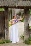 Η νύφη με μια ανθοδέσμη των λουλουδιών που θέτουν στη φωτογραφία στη φύση Στοκ φωτογραφία με δικαίωμα ελεύθερης χρήσης