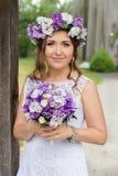 Η νύφη με μια ανθοδέσμη των λουλουδιών που θέτουν στη φωτογραφία στη φύση Στοκ Φωτογραφία