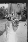 Η νύφη με μια ανθοδέσμη των λουλουδιών που θέτουν στη φωτογραφία στη φύση Στοκ Εικόνα