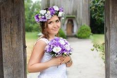 Η νύφη με μια ανθοδέσμη των λουλουδιών που θέτουν στη φωτογραφία στη φύση Στοκ Φωτογραφίες