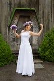 Η νύφη με μια ανθοδέσμη των λουλουδιών που θέτουν στη φωτογραφία στη φύση Στοκ Εικόνες