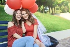Η νύφη με τη συνεδρίαση φίλων του στο πάρκο Κρατήστε τα μπαλόνια στοκ φωτογραφίες