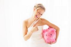 Η νύφη με τη piggy παρουσίαση τραπεζών φυλλομετρεί επάνω στοκ εικόνες με δικαίωμα ελεύθερης χρήσης