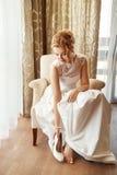 Η νύφη ντύνει τα παπούτσια Στοκ Εικόνες