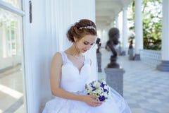 Η νύφη ομορφιάς στη νυφική εσθήτα με την ανθοδέσμη και η δαντέλλα καλύπτουν στη φύση στοκ φωτογραφία