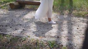 Η νύφη πηγαίνει στα άσπρα παπούτσια γυμναστικής και ένα μακρύ άσπρο φόρεμα απόθεμα βίντεο