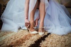 Η νύφη που παίρνει τα γαμήλια παπούτσια της επάνω Στοκ Φωτογραφίες