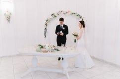 Η νύφη σε ένα άσπρο φόρεμα και ο νεόνυμφος σε ένα μπλε κοστούμι στέκονται κοντά σε μια αψίδα στο δωμάτιο και κρατούν μια γαμήλια  Στοκ φωτογραφία με δικαίωμα ελεύθερης χρήσης