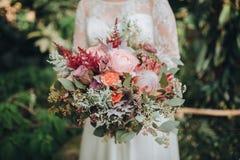 Η νύφη σε ένα άσπρο φόρεμα που στέκεται σε ένα πράσινο υπόβαθρο και κρατά μια γαμήλια ανθοδέσμη των λουλουδιών και των πρασίνων μ στοκ φωτογραφίες με δικαίωμα ελεύθερης χρήσης