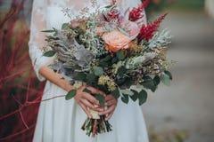 Η νύφη σε ένα άσπρο φόρεμα στέκεται και κρατά στα χέρια μια ανθοδέσμη των λουλουδιών και των πρασίνων με μια κορδέλλα στοκ εικόνες