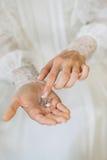 Η νύφη σε ένα γαμήλιο φόρεμα δαντελλών κρατά τα σκουλαρίκια με τα μαργαριτάρια Στοκ Εικόνα