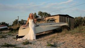Η νύφη σε ένα γαμήλιο φόρεμα στέκεται κοντά στη βάρκα απόθεμα βίντεο