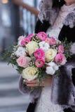Η νύφη στα όμορφα χειμερινά γάντια κρατά μια ανθοδέσμη χειμερινού γάμου Στοκ Φωτογραφίες
