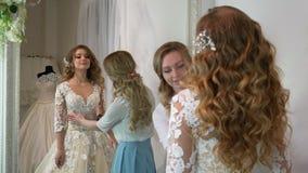 Η νύφη στο κατάστημα ενδυμάτων για το γάμο ντύνει αυτή επιλέγει ένα φόρεμα και ο σχεδιαστής την βοηθά απόθεμα βίντεο