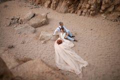 Η νύφη στο μακρύ φόρεμα και ο νεόνυμφος κάθονται και κρατούν παραδίδουν το φαράγγι στην άμμο Τοπ όψη Στοκ Εικόνες