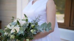 Η νύφη στο φόρεμα δαντελλών που κρατά τον όμορφο άσπρο και πράσινο γάμο ανθίζει την ανθοδέσμη, κινηματογράφηση σε πρώτο πλάνο φιλμ μικρού μήκους